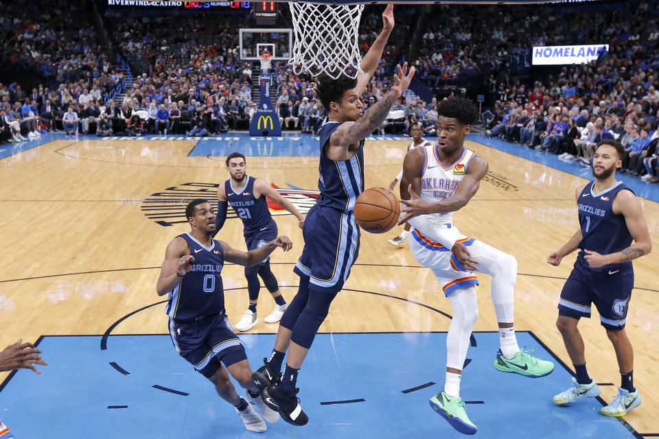 Photo - Oklahoma City's Shai Gilgeous-Alexander (2) passes the ball as Memphis' Brandon Clarke (15) and De'Anthony Melton (0) defend during an NBA basketball game between the Oklahoma City Thunder and the Memphis Grizzlies at Chesapeake Energy Arena in Oklahoma City, Wednesday, Dec. 18, 2019. Oklahoma City won 126-122. [Bryan Terry/The Oklahoman]