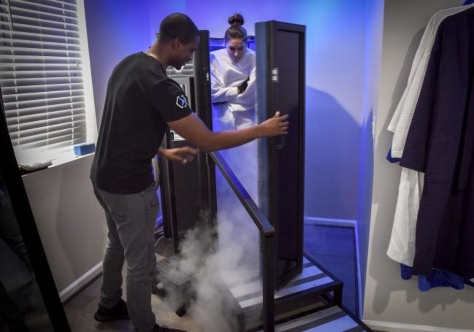 Photo -  Antwain Coward, left, opens the door to his cryotherapy device for customer Meredith Santora, right, at his shop in Washington, DC. [Bill O'Leary/Washington Post]