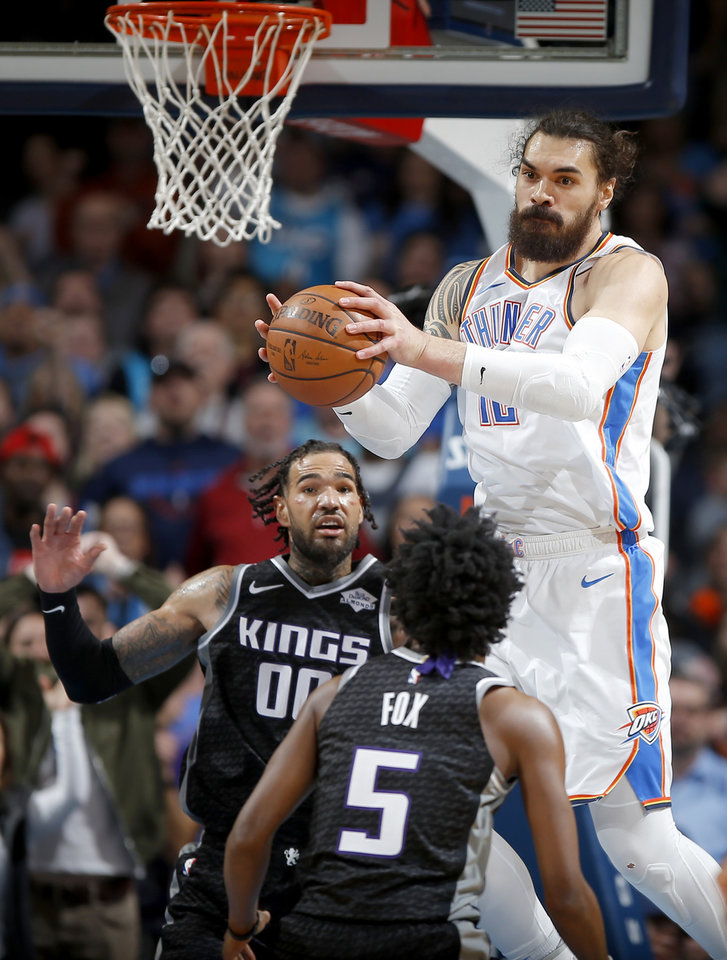 Photo - Oklahoma City's Steven Adams (12) grabs a rebound beside Sacramento's Willie Cauley-Stein (00) during an NBA basketball game between the Oklahoma City Thunder and the Sacramento Kings at Chesapeake Energy Arena in Oklahoma City, Saturday, Feb. 23, 2019. Sacramento won 119-116. Photo by Bryan Terry, The Oklahoman