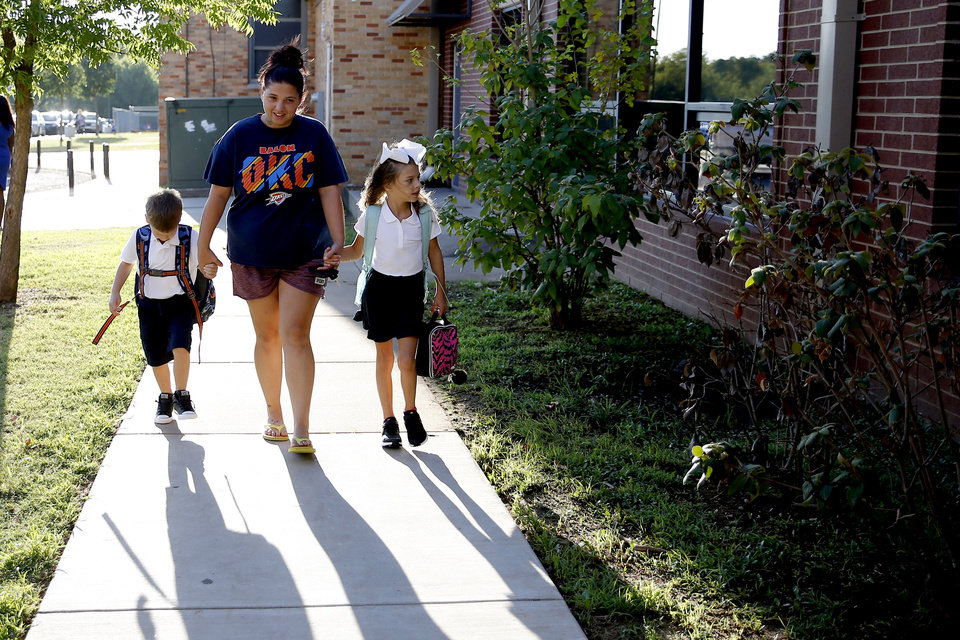 Photo - Kyle Kennedy, walks with her children, kindergartner Braylon Hart, 5, at left, and third-grader Rexlyn Hibdon, 8, towards Britton Elementary during the first of school in Oklahoma City, Monday, Aug. 12, 2019. [Bryan Terry/The Oklahoman]