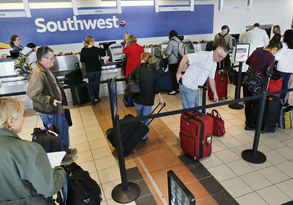 Photo -  Travelers line up at the Southwest Airlines counter at Will Rogers World Airport in Oklahoma City. [Photo by Paul Hellstern, The Oklahoman archives]