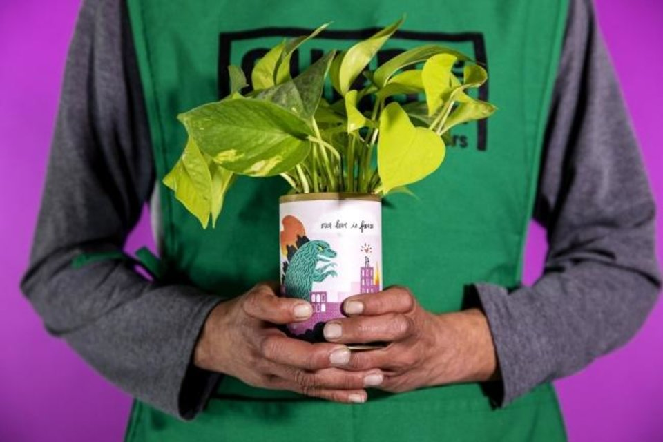 Photo -  John holds a plant at Curbside Flowers, a new full-service flower shop that is a program of the Homeless Alliance.  Every bouquet is made by a Curbside vendor, providing meaningful employment to someone transitioning out of homelessness. [Photo provided by Nathan Poppe]