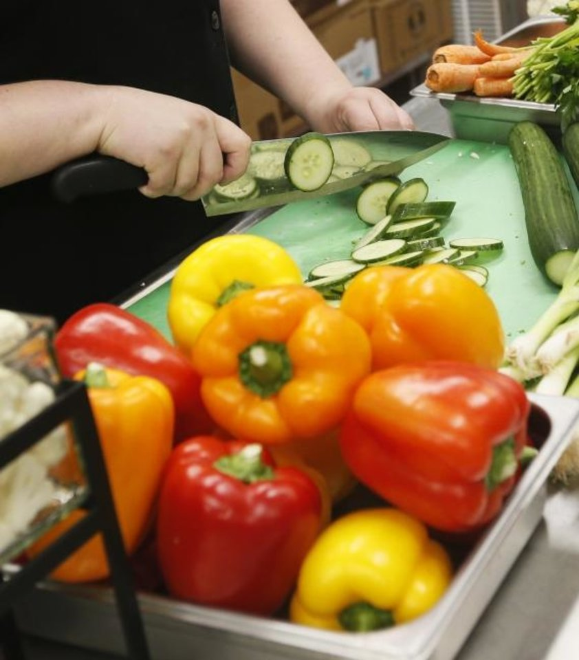Photo -  Katherine Halseide, executive chef and director of catering at St. Luke's, chops vegetables in the kitchen at St. Luke's United Methodist Church, 222 NW 15, where church volunteers prepare Mobile Meals for homebound older adults in the metro area. Halseide has helped St. Luke's as it launches its Ending Hunger OKC initiative. [Nate Billings/The Oklahoman]