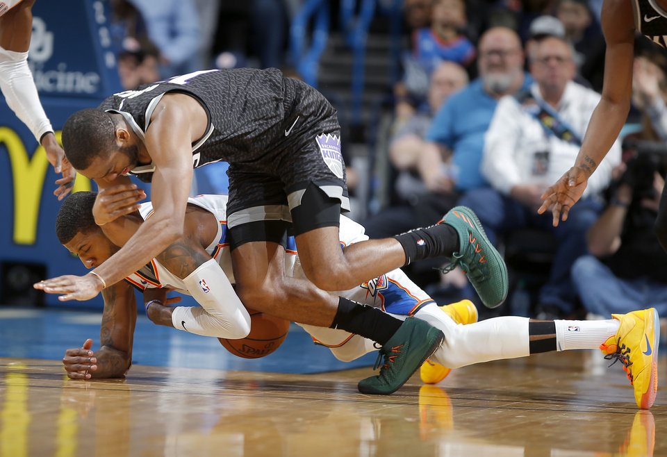 Photo - Oklahoma City's Paul George (13) dives for the ball under Sacramento's Alec Burks during an NBA basketball game between the Oklahoma City Thunder and the Sacramento Kings at Chesapeake Energy Arena in Oklahoma City, Saturday, Feb. 23, 2019. Sacramento won 119-116. Photo by Bryan Terry, The Oklahoman