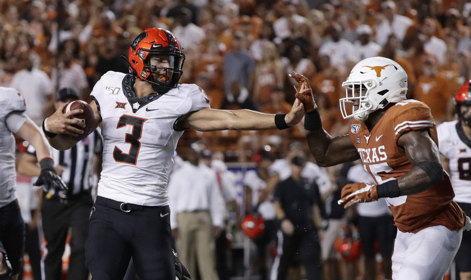 Photo - Oklahoma State quarterback Spencer Sanders (3) tries to hold off Texas defensive back Chris Brown (15) on a run during the second half of an NCAA college football game Saturday, Sept. 21, 2019, in Austin, Texas. (AP Photo/Eric Gay)