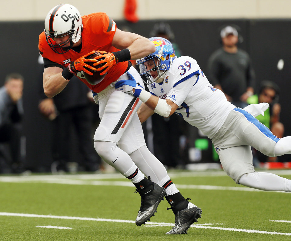 Photo - Oklahoma State's Blake Jarwin (47) makes a catch against Kansas' Michael Glatczak (39) during a college football game between the Oklahoma State University Cowboys (OSU) and the Kansas Jayhawks (KU) in Stillwater, Okla., Saturday, Oct. 24, 2015. Photo by Nate Billings, The Oklahoman