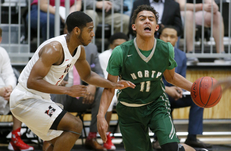 Photo - Norman North's Trae Young goes around Mustang's Jakolby Long during a basketball game between Mustang and Norman North in Mustang, Okla., Tuesday, Feb. 16, 2016. Photo by Bryan Terry, The Oklahoman