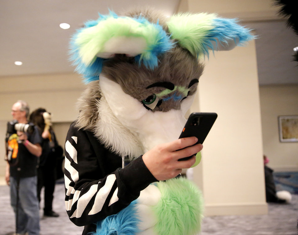 Photo - Aspen looks at his phone during the AnthroExpo 2020 at the Sheraton Oklahoma City Downtown Hotel, Friday, Jan. 31, 2020.  [Sarah Phipps/The Oklahoman]
