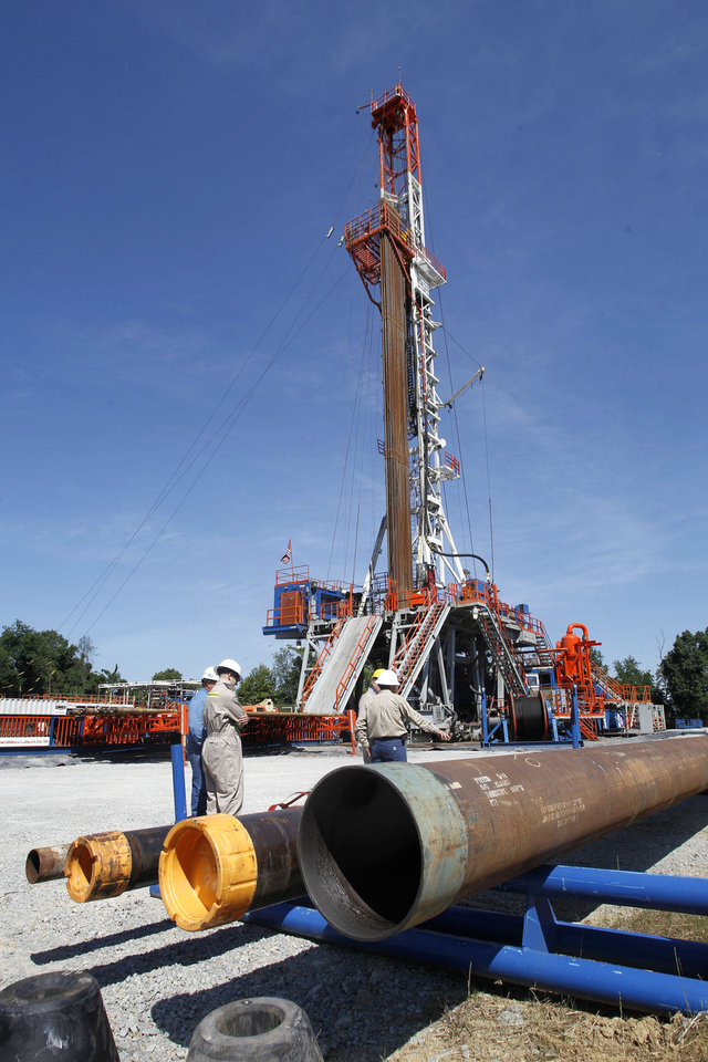 Photo - Range Resources workers stand near a rig that drills into the shale at a well site in Washington, Pa.  AP File Photo