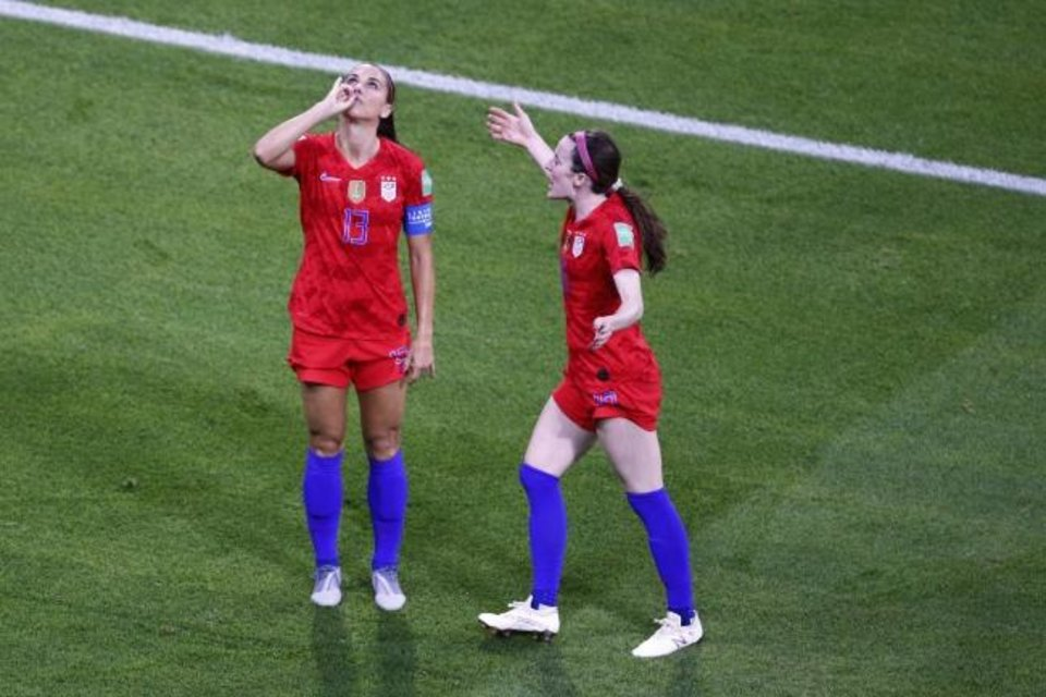 Photo -  United States' Alex Morgan, left, celebrates her goal against England by pretending to drink a cup of tea during Tuesday's game at the World Cup in Lyon, France. [AP Photo/Francois Mori]