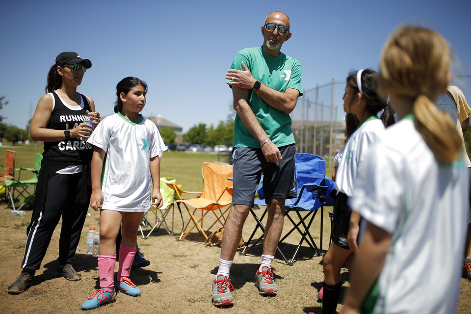 Photo -  Estabraq Al-Adhami, with his wife, Nassil Abdullah, talks with some of his players and his daughter Hala, 9, after coaching the last game of the season in Oklahoma City. [Photo by Bryan Terry, The Oklahoman]