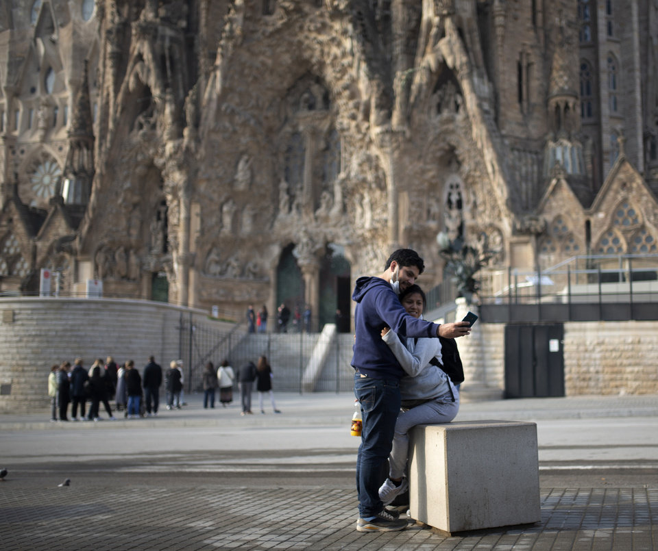 Photo -  People take a selfie outside the Sagrada Familia basilica in Barcelona, Spain, Friday. The basilica closed its doors to visitors and suspend construction from Friday, March 13 to prevent the spread of the new COVID-19 coronavirus. Spain, along with Italy and France, is among the countries worst hit by the virus so far in Europe. [Joan Mateu/the associated press]