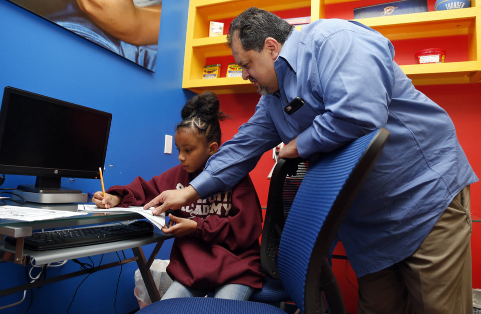 Photo -  Rey Medrano, elementary and middle school principal, helps Tanari Bailey, 8, at the Justice Alma Wilson SeeWorth Academy at 12600 N. Kelley Ave. in Oklahoma City, Wednesday, Feb. 17, 2016. [Nate Billings/The Oklahoman]