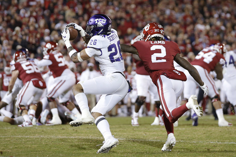 Photo - TCU's Vernon Scott (26) intercepts a pass intended for Oklahoma's CeeDee Lamb (2) before returning it for a touchdown during an NCAA football game between the University of Oklahoma Sooners (OU) and the TCU Horned Frogs at Gaylord Family-Oklahoma Memorial Stadium in Norman, Okla., Saturday, Nov. 23, 2019. Oklahoma won 28-24. [Bryan Terry/The Oklahoman]