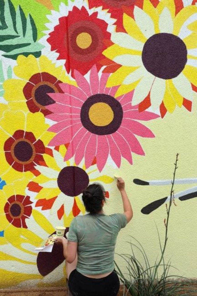 Photo -  Kaylee Jones W. helps to paint Amanda Weather's mural,