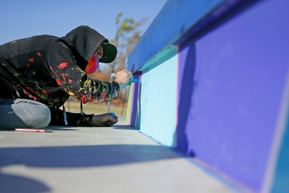 Photo -  Muralist Dylan Bradway paints a mural on the vertical surfaces of the skate park at Stars and Stripes Park in Oklahoma City. [Bryan Terry photos/The Oklahoman]
