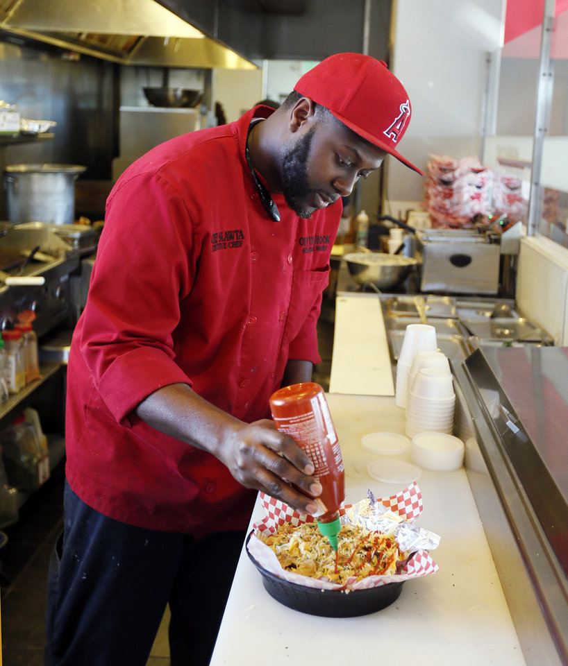 Photo - Chef Corey Harris makes smothered seafood fries at Off the Hook Seafood and More, 125 W. Britton Rd., in Oklahoma City. [Photo by Nate Billings, The Oklahoman]