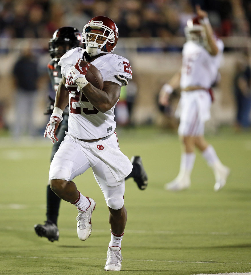 Photo - Oklahoma's Joe Mixon (25) runs for a touchdown as Baker Mayfield (6) celebrates in the background in the fourth quarter of a college football game between the University of Oklahoma Sooners (OU) and Texas Tech Red Raiders at Jones AT&T Stadium in Lubbock, Texas, Saturday, Oct. 22, 2016. OU won 66-59. Photo by Nate Billings, The Oklahoman