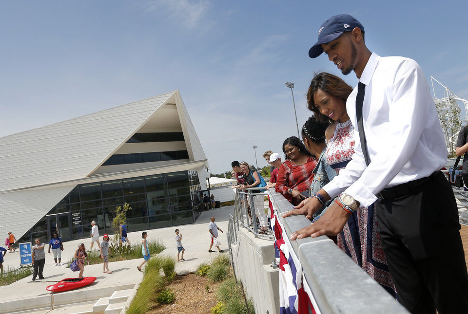 Photo - Oklahoma City's Terrance Ferguson his mom Rachelle Holdman watch rafters at the  RIVERSPORT Rapids following an introductory press conference a the CHK | Central Boathouse in Oklahoma City, Saturday, June 24, 2017. Photo by Sarah Phipps, The Oklahoman
