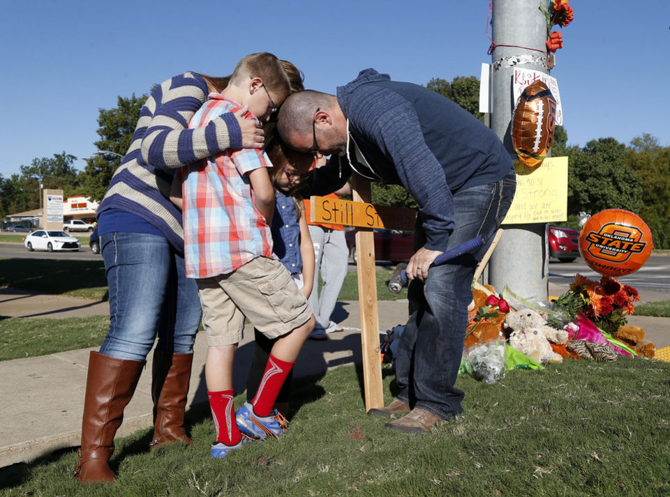 Photo -  Matthew Skar, right, prays Sunday with his wife, Kali Skar, son Braxton Skar and daughter Sadie Blue Skar near a roadside memorial to victims of a fatal car crash at Oklahoma State University in Stillwater. [photo by MATT BARNARD, Tulsa World]