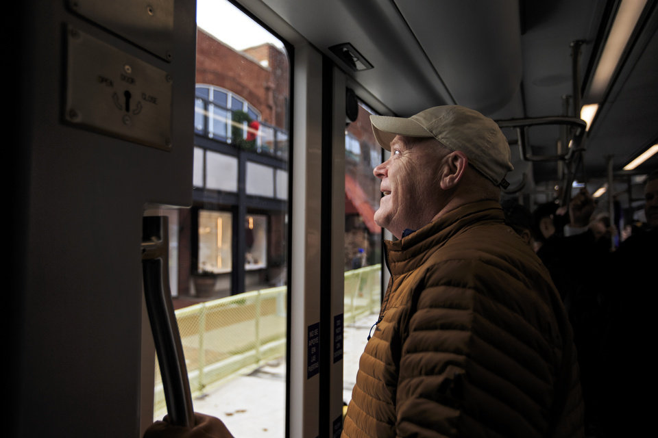 Photo - Passenger Mark Lester looks out the window as he gets a free ride on the new streetcar during the grand opening celebration day of the Oklahoma City streetcar system in downtown Oklahoma City, Okla. on Friday, Dec. 14, 2018. Photo by Chris Landsberger, The Oklahoman