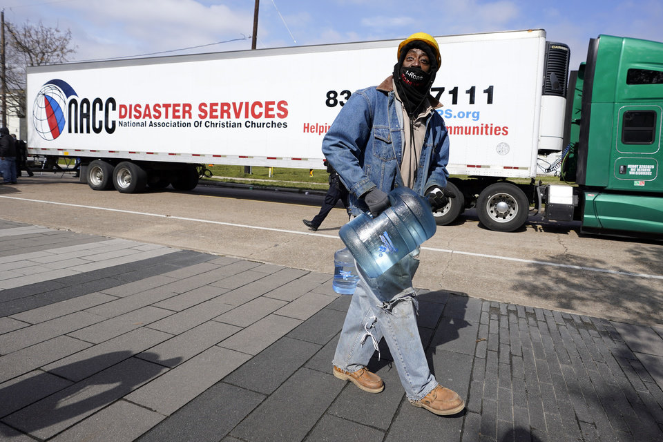Photo -  James White carries a bottle of donated water from a distribution site Thursday, Feb. 18, 2021, in Houston. Houston and several surrounding cities are under a boil water notice as many residents are still without running water in their homes. (AP Photo/David J. Phillip)