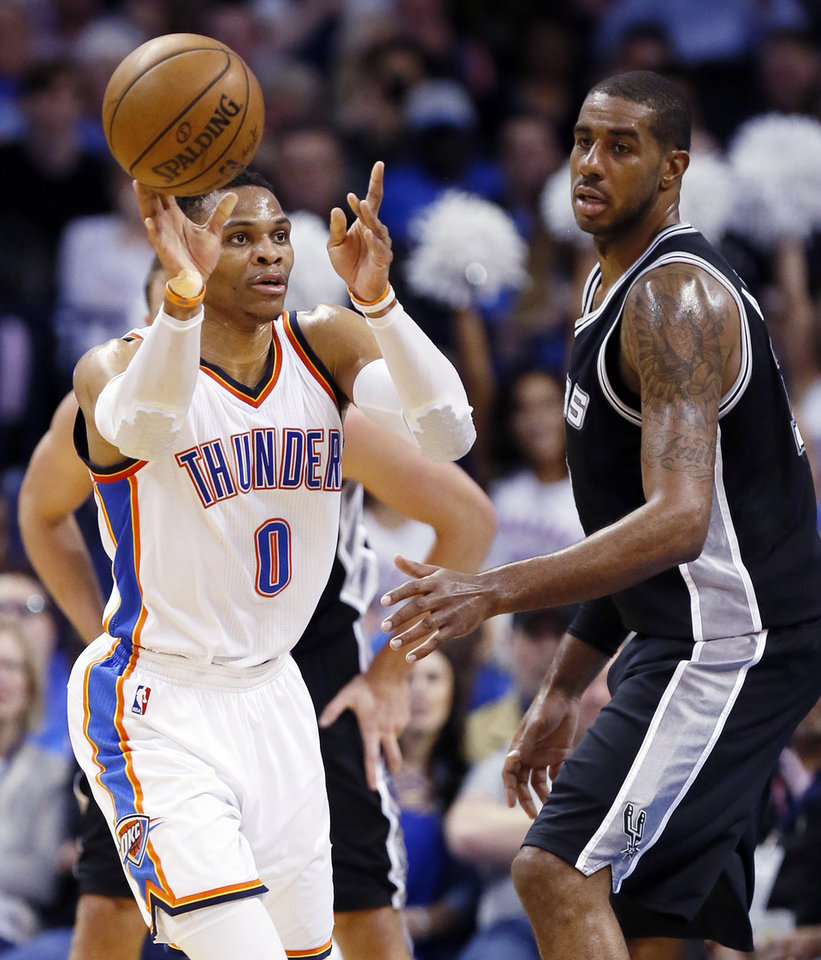 Photo - Oklahoma City's Russell Westbrook (0) passes away from LaMarcus Aldridge (12) during an NBA basketball game between the Oklahoma City Thunder and San Antonio Spurs at Chesapeake Energy Arena in Oklahoma City, Friday, March 31, 2017. Photo by Nate Billings, The Oklahoman