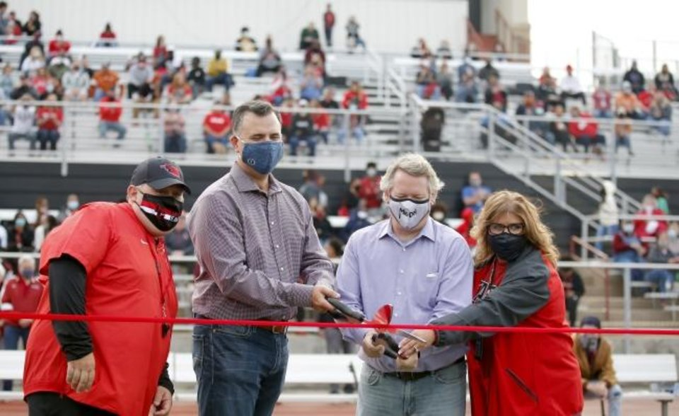 Photo -  Robert Kalsu Jr. (second from left) cuts the ribbon during a dedication of the Del City Stadium named after his father, Robert Kalsu, before Friday's game against Carl Albert. [Sarah Phipps/The Oklahoman]