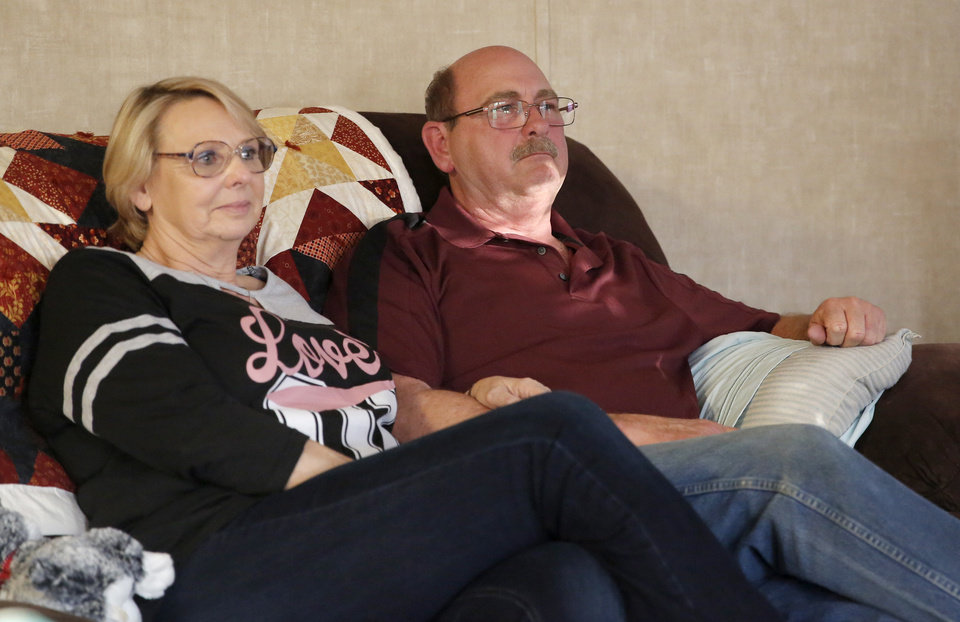 Photo -  Carolyn and Don Parnell watch a memorial video for their daughter, Desirae, at their home in Newalla. Desirae Parnell was shot to death by her ex-boyfriend in December 2016. [Photo by Sarah Phipps, The Oklahoman]