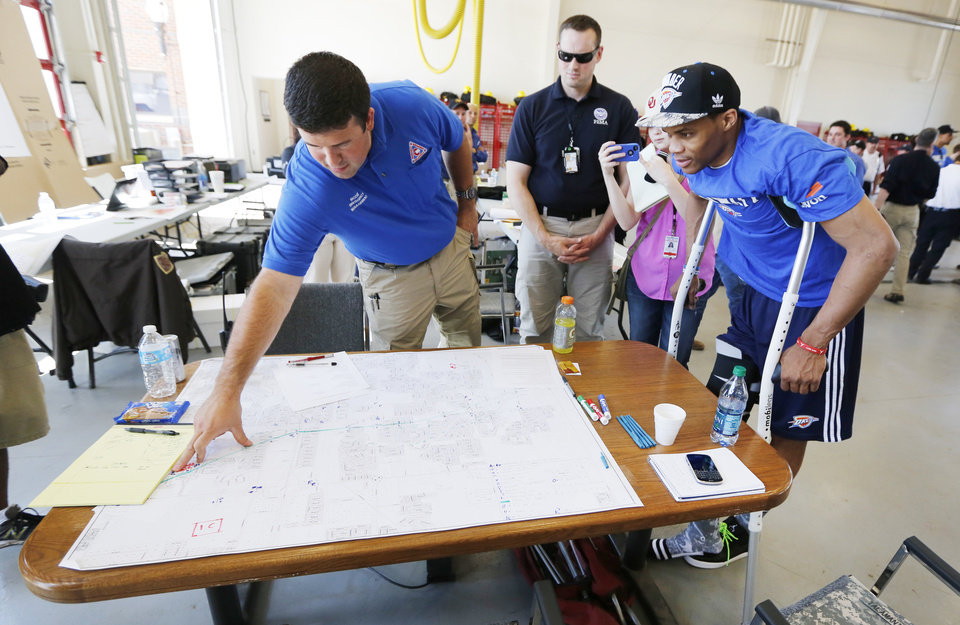 Photo - Oklahoma City Thunder's Russell Westbrook looks at a map with rescue workers at a command center in Moore, Wednesday May 22, 2013. Members of the Oklahoma City Thunder and family members took a tour of the area hit by a tornado on Monday afternoon. Photo By Steve Gooch, The Oklahoman