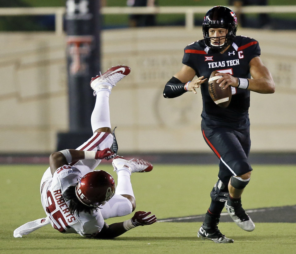 Photo - Texas Tech's Patrick Mahomes II (5) breaks away from Oklahoma's Austin Roberts (95) as Roberts holds the nameplate he pulled off the back of Mahomes' jersey in the third quarter during a college football game between the University of Oklahoma Sooners (OU) and Texas Tech Red Raiders at Jones AT&T Stadium in Lubbock, Texas, Saturday, Oct. 22, 2016. OU won 66-59. Photo by Nate Billings, The Oklahoman