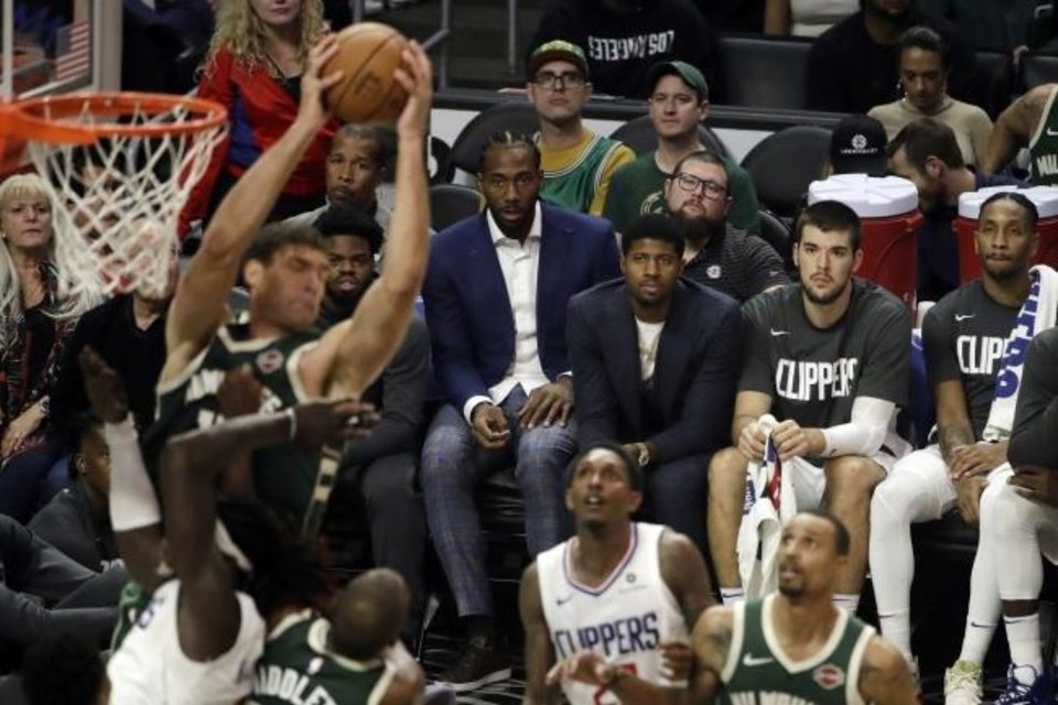 Photo -  Clippers forwards Kawhi Leonard, center, and Paul George, third from right, watch from the bench during a game against the Bucks on Wednesday in Los Angeles. [AP Photo/Marcio Jose Sanchez]
