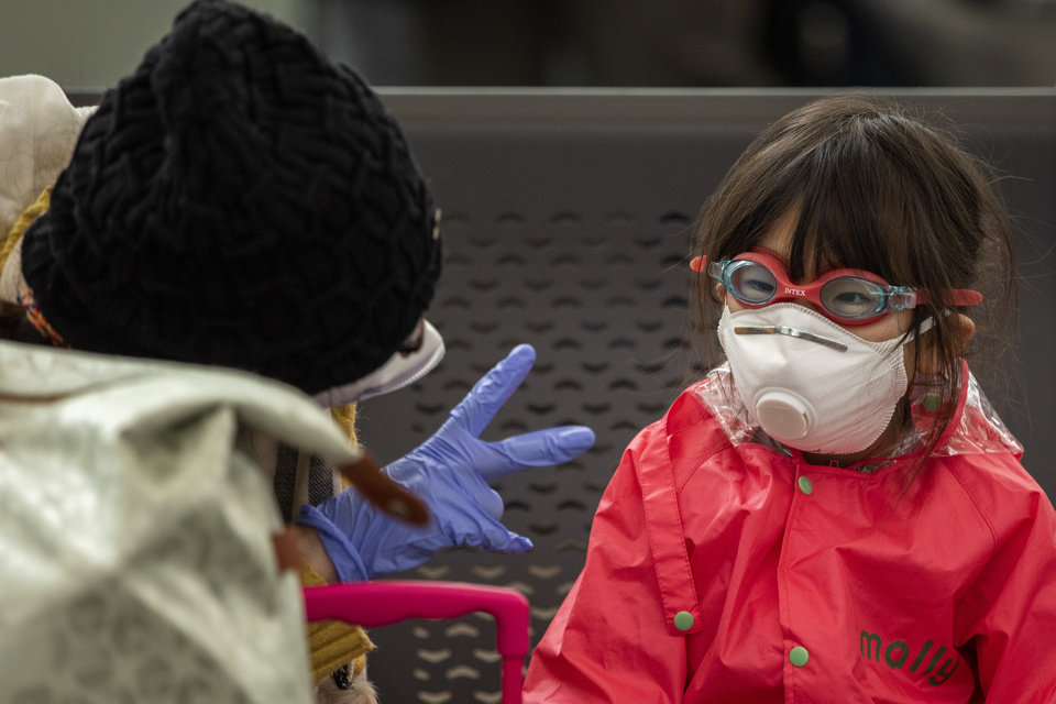 Photo -  A woman plays with her daughter as they wait at Barcelona airport, Spain, Saturday, March 14, 2020. Spain's prime minister has announced a two-week state of emergency from Saturday in a bid to contain the new coronavirus outbreak. For most people, the new coronavirus causes only mild or moderate symptoms. For some, it can cause more severe illness, especially in older adults and people with existing health problems. (AP Photo/Emilio Morenatti)
