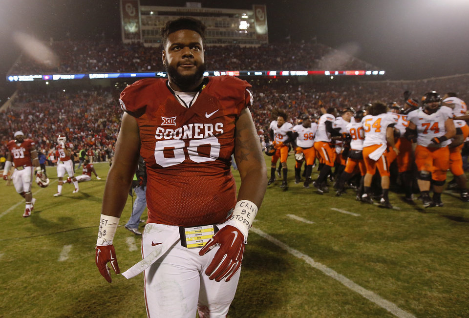 Photo - Oklahoma's Jordan Phillips (80) walks off the field as Oklahoma State celebrates after winning the Bedlam college football game between the University of Oklahoma Sooners (OU) and the Oklahoma State Cowboys (OSU) at Gaylord Family-Oklahoma Memorial Stadium in Norman, Okla., Saturday, Dec. 6, 2014. Photo by Bryan Terry, The Oklahoman