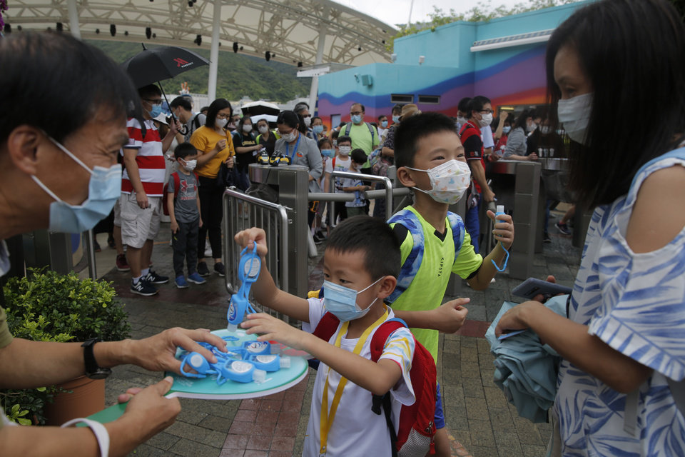 Photo -  Guests wearing face masks to prevent the spread of the new coronavirus, receive hand sanitizer at Ocean Park in Hong Kong, Saturday, June 13, 2020. Hong Kong Ocean Park reopened Saturday after nearly four months of closure due to the coronavirus pandemic. The animal and nature-themed attraction combines pandas, penguins, roller coasters and other rides, and has been a Hong Kong icon since its opening in 1977. (AP Photo/Kin Cheung)