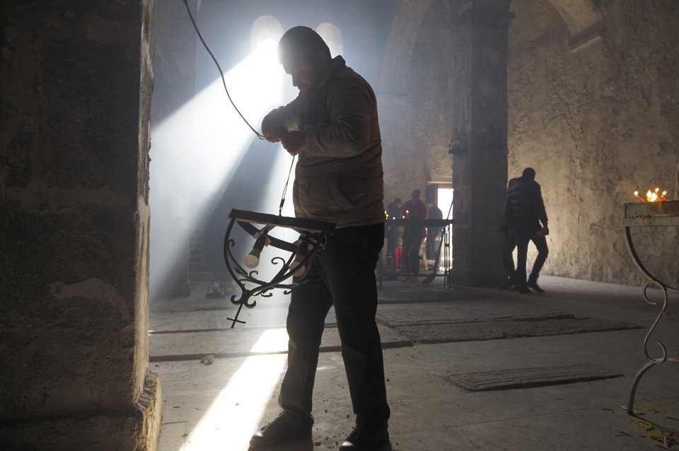 Photo -  A man removes lamps inside a church of the Dadivank, an Armenian Apostolic Church monastery dating to the 9th century, as ethnic Armenians leave the separatist region of Nagorno-Karabakh to Armenia, Saturday, Nov. 14, 2020. The territory is to be turned over to Azerbaijan on Sunday as part of territorial concessions in an agreement to end six weeks of intense fighting with Armenian forces. Hundreds of thousands of Azeris were displaced by the war that ended in 1994. It is unclear when any civilians might try to settle in Karvachar — which will now be known by its Azeri name Kalbajar — or elsewhere. (AP Photo/Dmitry Lovetsky)