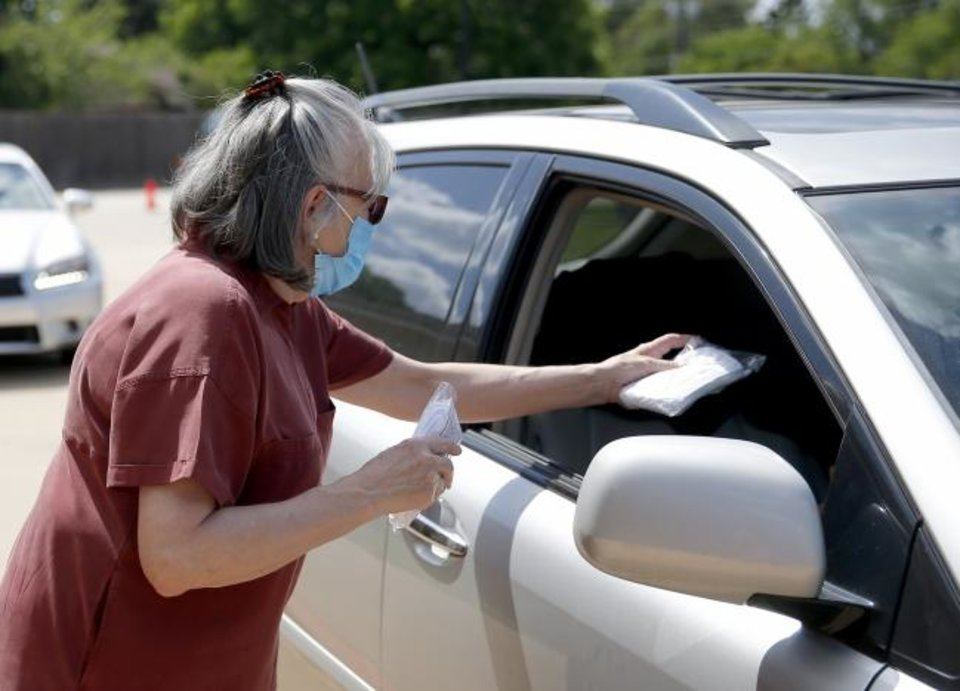 Photo -  Volunteer Brenda Hoopers hands out a pack of free masks during a  drive-thru mask distribution at Chabad Community Center for Jewish Life and Learning, 3000 W Hefner Road. [Sarah Phipps/The Oklahoman]