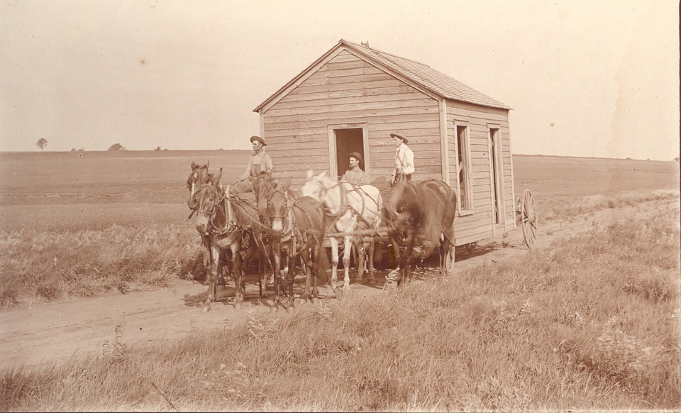 Photo -  Settlers move a frame house across wide-open prairie near Perry in pre-statehood Oklahoma. [PHOTO PROVIDED BY OKLAHOMA HISTORICAL SOCIETY]