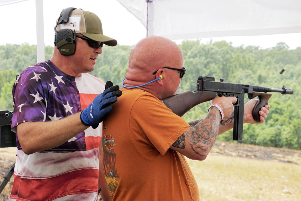 Photo - Coby Snyder, left, helps Derrick Jervis aim at a target at the Oklahoma Full Auto Shoot and Trade Show Saturday in Wyandotte. [Jordan Green/The Oklahoman]