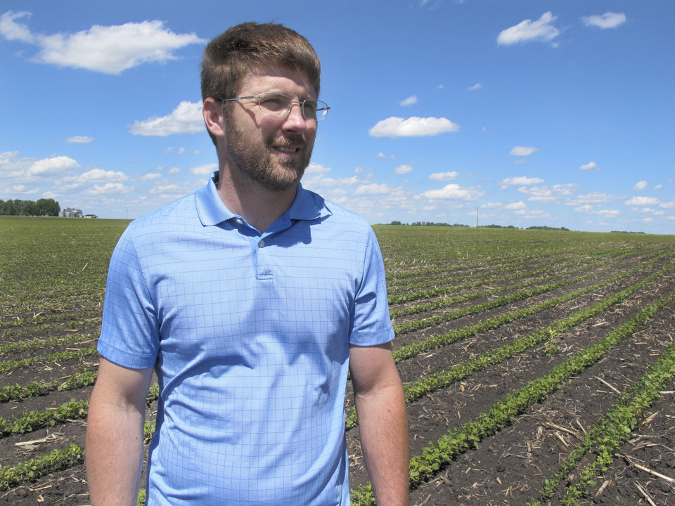 Photo -  In this Tuesday, June 25, 2019, photo, farmer Matthew Keller walks in his soybean field near Kenyon, Minn. When the Trump administration announced a $12 billion aid package for farmers struggling under the financial strain of his trade dispute with China, the payments were capped. But records obtained by The Associated Press under the Freedom of Information Act show that many large farming operations easily found legal ways around the limits to collect big checks. Recipients who spoke to AP defended the payouts, saying they didn't even cover their losses under the trade war and that they were legally entitled to them. Keller, a pork producer in Kenyon, who also grows crops to feed his livestock, said he