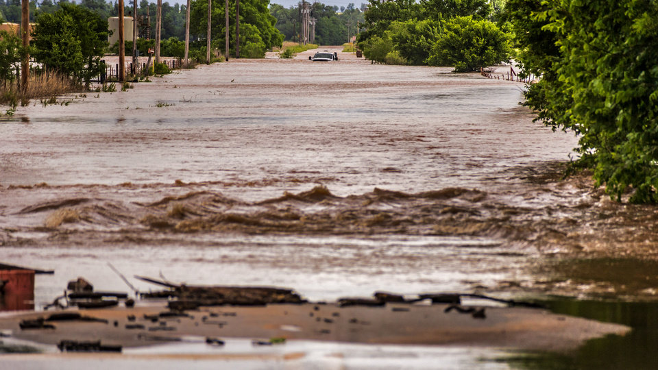 Photo - A truck is stranded in flood waters on Radio Rd. near Elm St. after heavy rains flooded areas in El Reno, Okla. on Monday, May 20, 2019.  [Chris Landsberger/The Oklahoman]