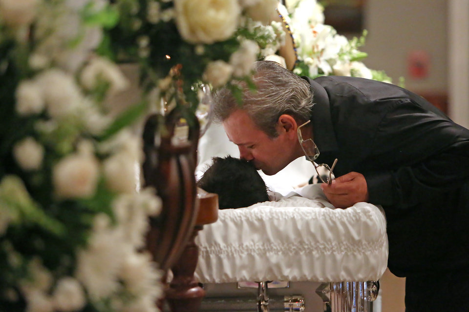 Photo - Juan Flores Sr., along with family and friends, leans over to