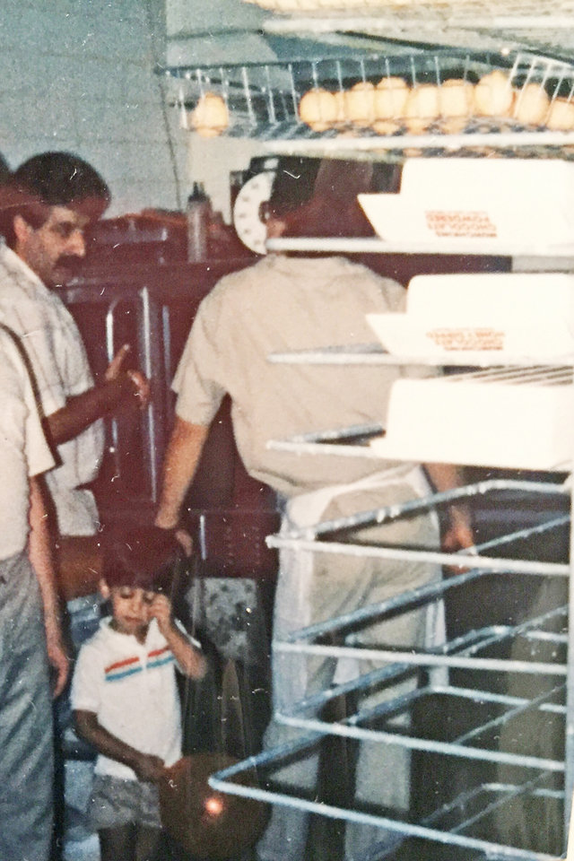 Photo -  A young Misha Goli stands at the side of his father, Massoud Goli, in the kitchen of the immigrant's first Dunkin' Donuts at NW 32 and Classen Boulevard. Misha Goli is now a second-generation franchisee and is opening his ninth store at NW 23 and Hudson Avenue. [Photo provided]