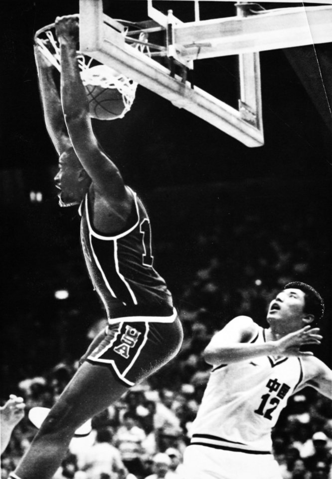 Photo - Former OU basketball player Wayman Tisdale. LOS ANGELES, July 30-DOMINATING DUNK-Wayman Tisdale executes a reverse dunk as China's Libin Wang (12) looks on in awe during Olympic basketball competition in Los Angeles Sunday. The U.S. won the game 97-49. (AP LaserPhoto) 1984. Photo taken 7/30/1984, photo published 7/30/1984 in The Daily Oklahoman. ORG XMIT: KOD