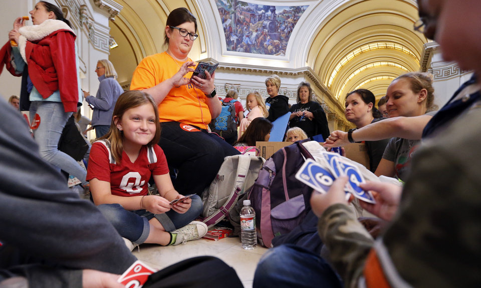 Photo -  Celest Wisniewski, 10, plays cards with her brother Corbyn, 6, beside her mother, Noel, under the fourth-floor rotunda as teachers participate in a walkout at the Oklahoma State Capitol building on Thursday in Oklahoma City. Noel Wisniewski is a teacher at Northridge Elementary in the Putnam City district and the family has been at the Capitol all four days. [Photo by Steve Sisney, The Oklahoman]