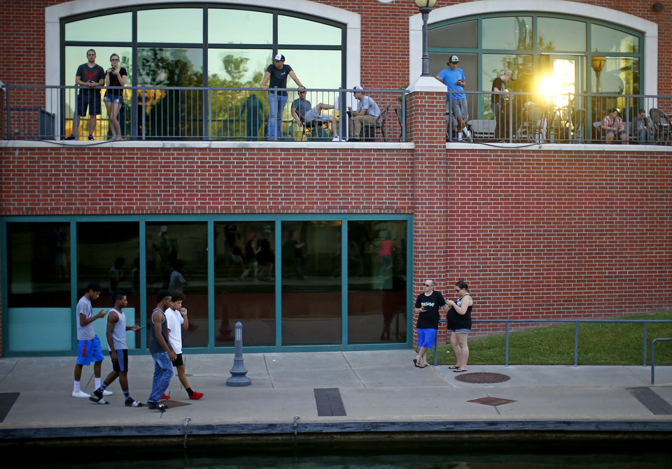 Photo - People play Pokemon Go along the Bricktown Canal during a meetup for players of the game in Oklahoma City at Bricktown on Friday, July 29, 2016. Photo by Bryan Terry, The Oklahoman