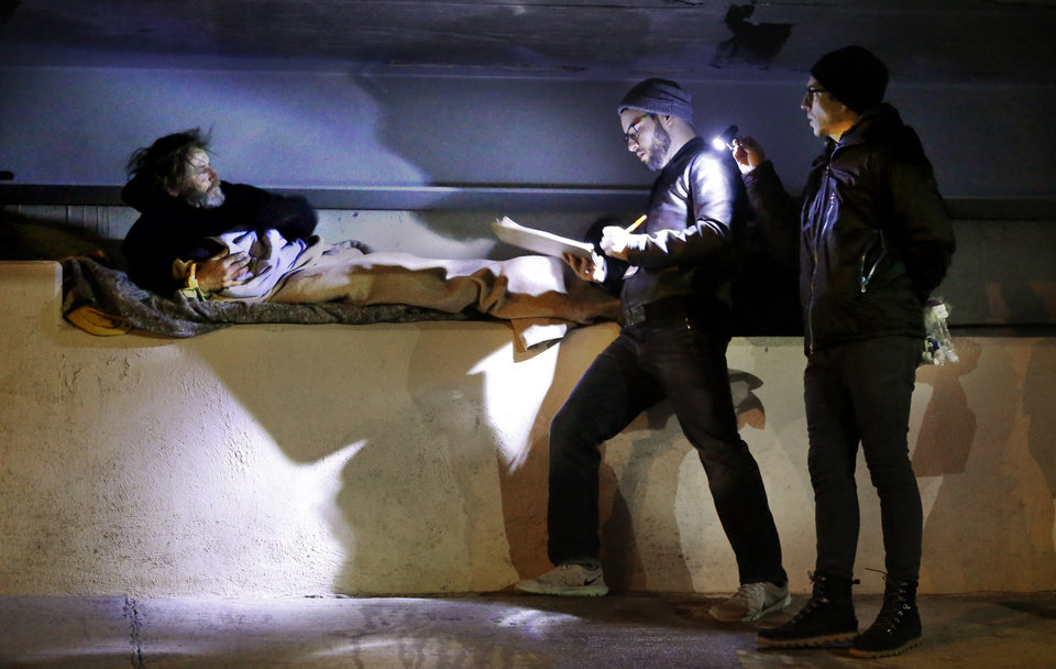 Photo -  Andru Dallaly, center, and Joe Hudson, right, interview Cotton Russell under an overpass before dawn Thursday during the city's annual Point-in-Time homeless count. [Photo by Steve Sisney, The Oklahoman]