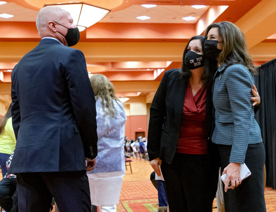 Photo - Commissioner of Health, Lance Frye, left, looks as Oklahoma's 2020 teacher of the year, Jena Nelson hugs Oklahoma Superintendent of Public Instruction, Joy Hofmeister, right, after Nelson received her Covid-19 vaccine during a vaccination pod at the Embassy Suites by Hilton Norman Hotel & Conference Center in Norman, Okla. on Monday, Feb. 22, 2021.  [Chris Landsberger/The Oklahoman]