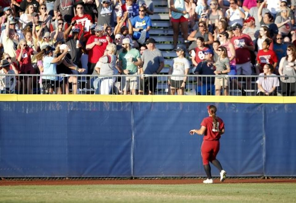Photo -  Oklahoma outfielder Nicole Mendes (11) watches a home run by UCLA's Briana Perez sail over the fence in the first inning Tuesday at USA Softball Hall of Fame Stadium. [Sarah Phipps/The Oklahoman]