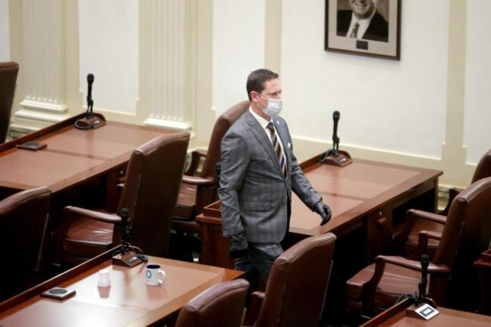 Photo - Rep. Brian Hill walks to his desk before a special session of the House of Representatives at the state Capitol in Oklahoma City, Monday, April 6, 2020. A skeleton crew of lawmakers was allowed in the House chamber as others watched from their offices during a special session of the House of Representatives. [Bryan Terry/The Oklahoman]